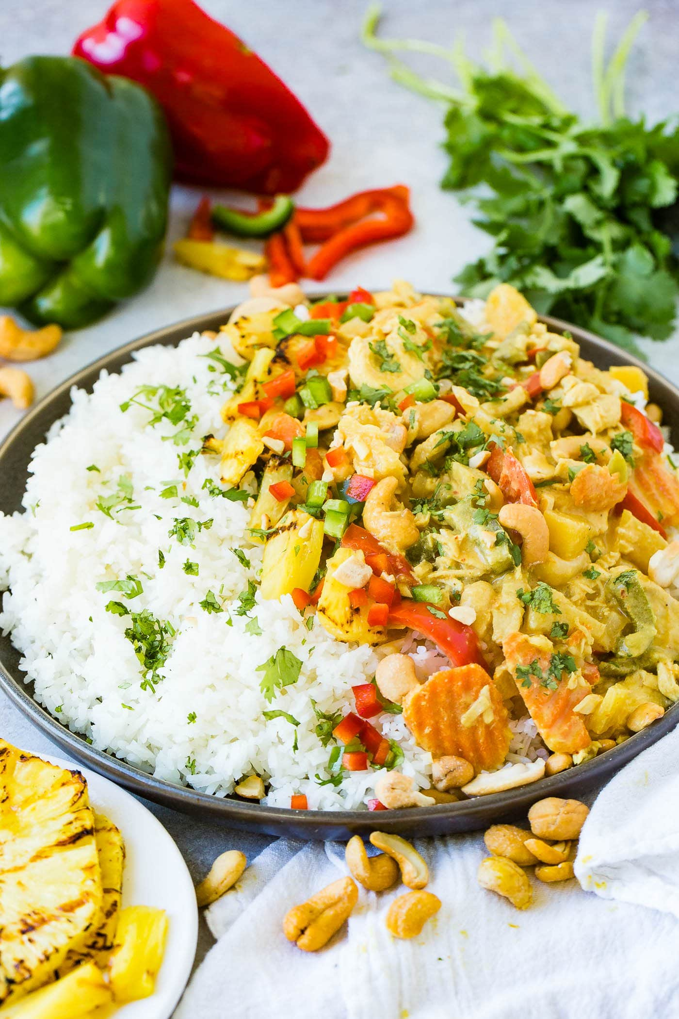 a plate with jasmine white rice piled with a creamy pineapple coconut curry sauce, peppers, onions and cashews with grilled pineapple