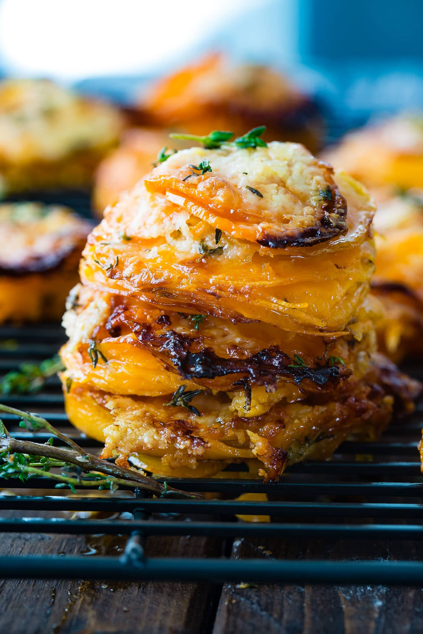 A photo of a stack of thinly sliced sweet potatoes layered with gruyere and parmesan cheese and topped with fresh thyme.