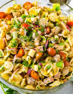 A photo of a cuban pasta salad with pork, ham, cubed swiss cheese, tomatoes, purple onions, and fresh herbs.