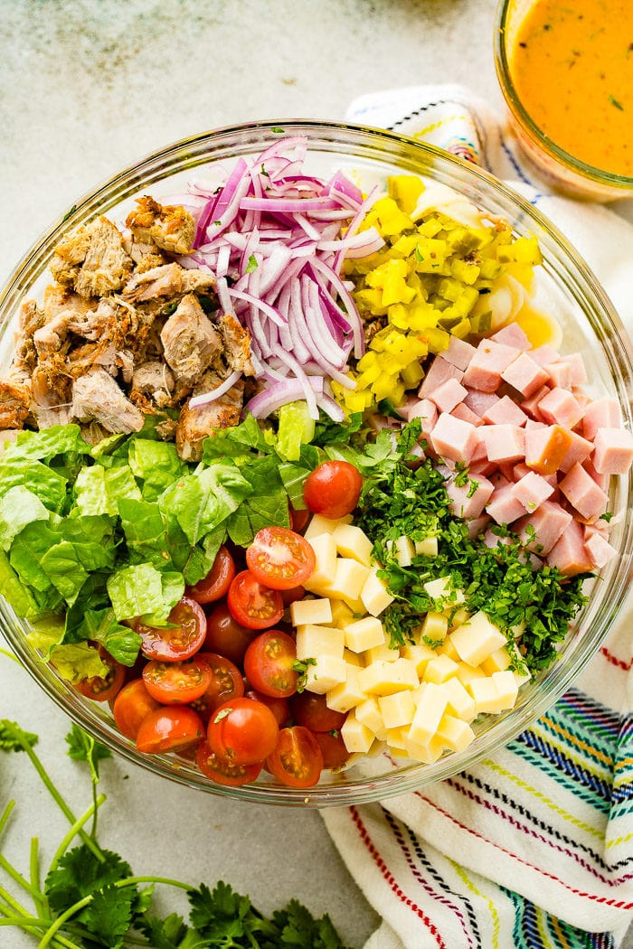 A photo of a large glass bowl full of all the ingredients for cuban pasta salad.