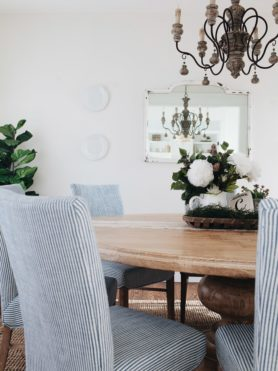 French Country Dining Room in white with natural wood, blue and white striped chairs, italian chandelier and round dining room table with pedestal leg ohsweetbasil.com