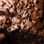 A close up photograph of a slice being picked up from a loaf of chocolate banana bread with mini chocolate chips all over the top that are starting to melt. The very best double chocolate banana bread