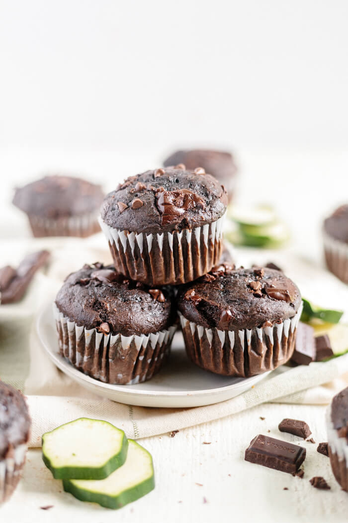 four chocolate zucchini muffins on white plate