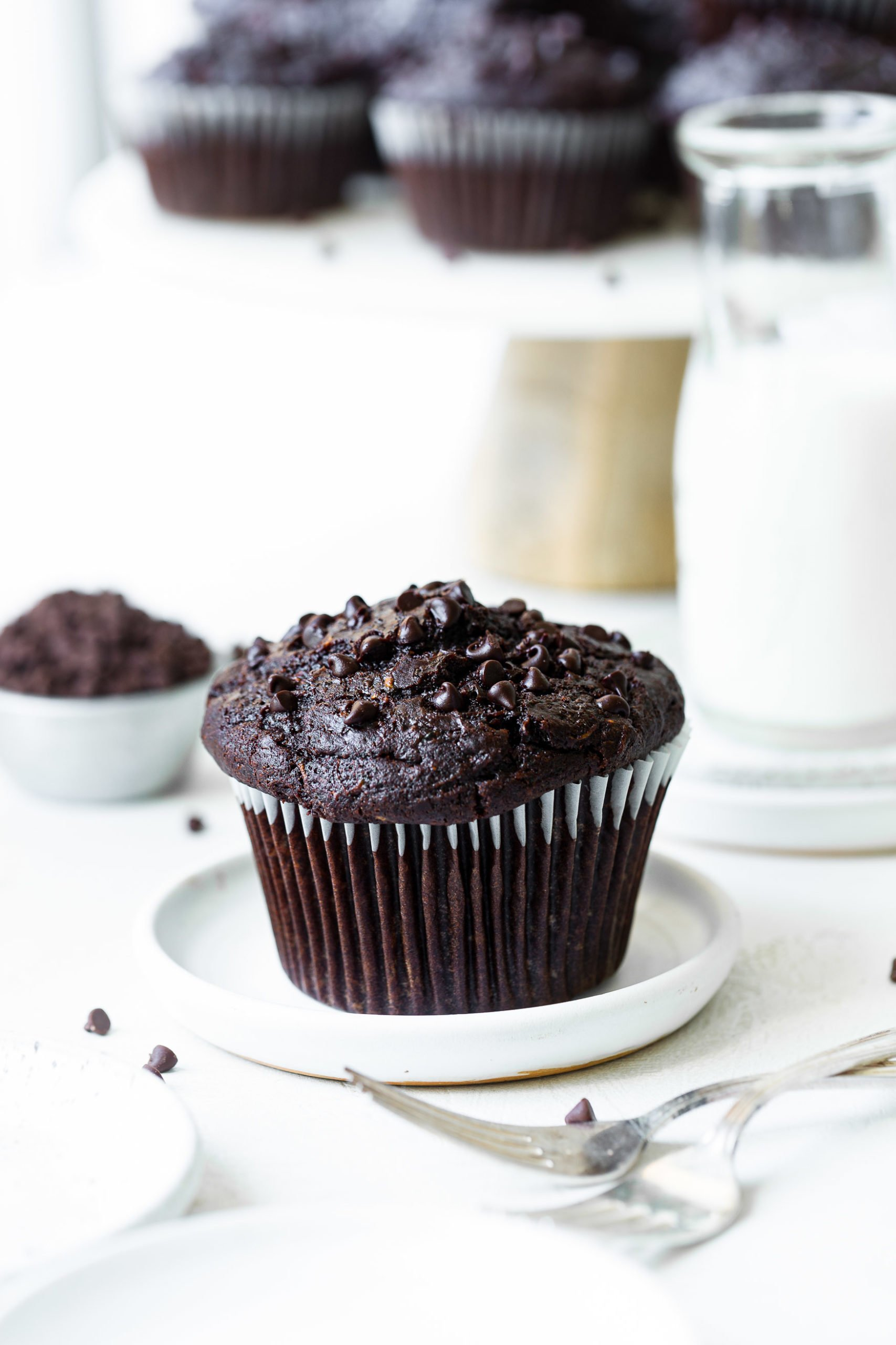 A white plate holding a jumbo chocolate zucchini muffin with mini chocolate chips on top