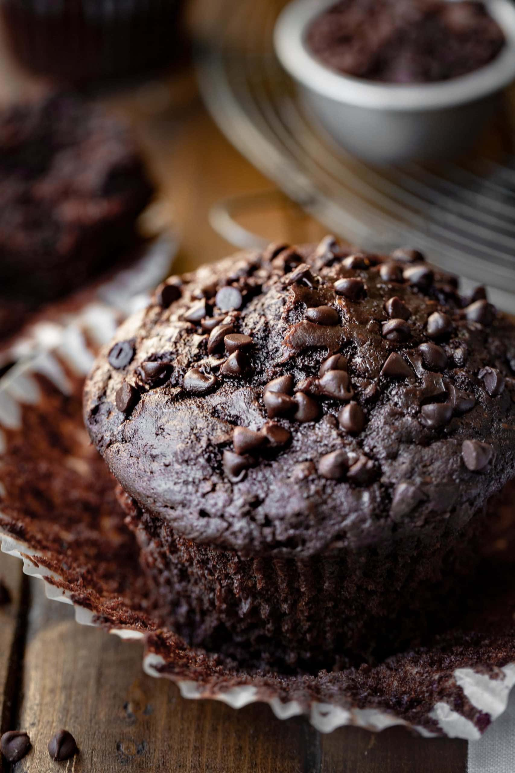 a tall double chocolate zucchini muffin with mini chocolate chips sitting on a wooden counter being unwrapped from a paper muffin liner