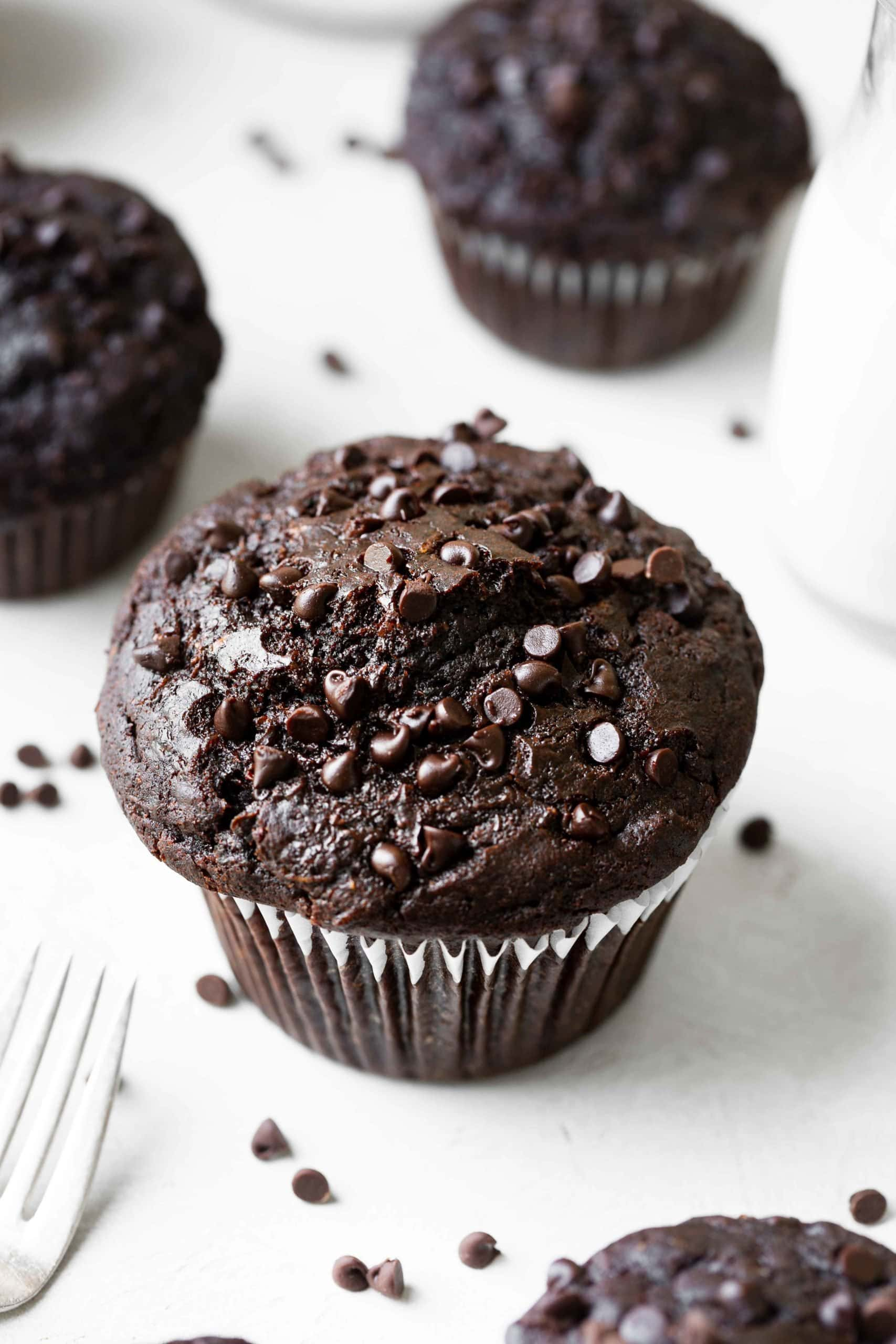 A white plate holding a jumbo chocolate zucchini muffin with mini chocolate chips on top and sprinkled around the moist chocolate muffin