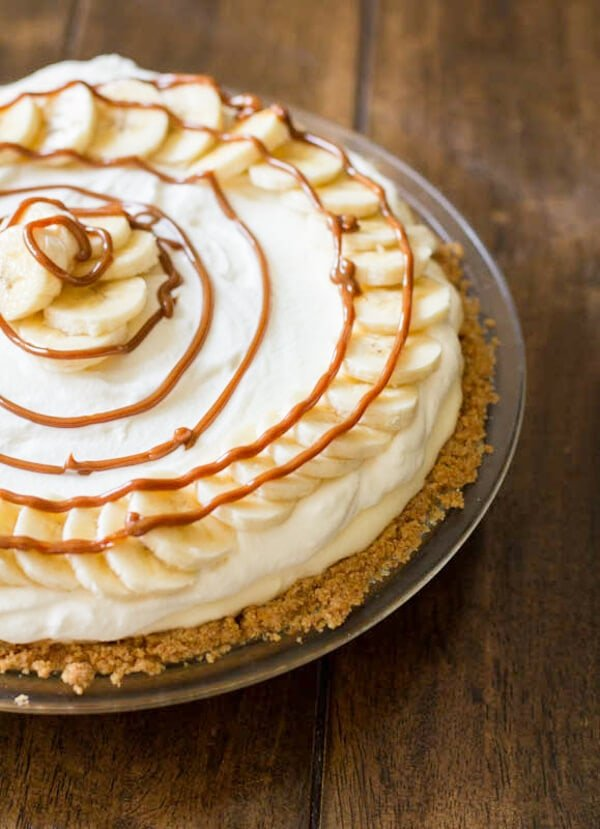 dulce de leche banana cream pie drizzled with caramel on a wooden table.