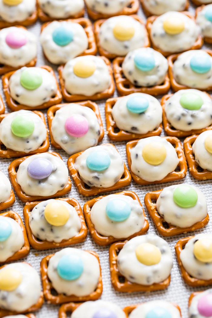 Many mini pretzels lined on a baking sheet with barely melted hershey's hugs topped with easter colored m&ms. Easter Pretzel Hugs with m&ms!