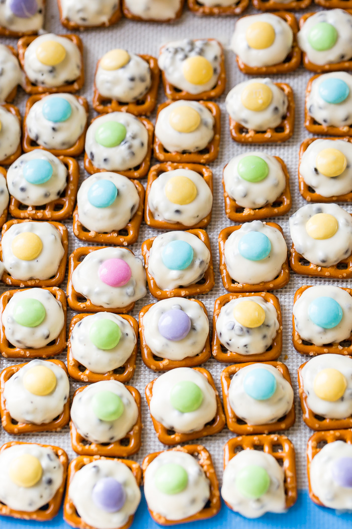 Mini pretzels topped with a barely melted hershey's cookies n cream hugs and an easter m&m