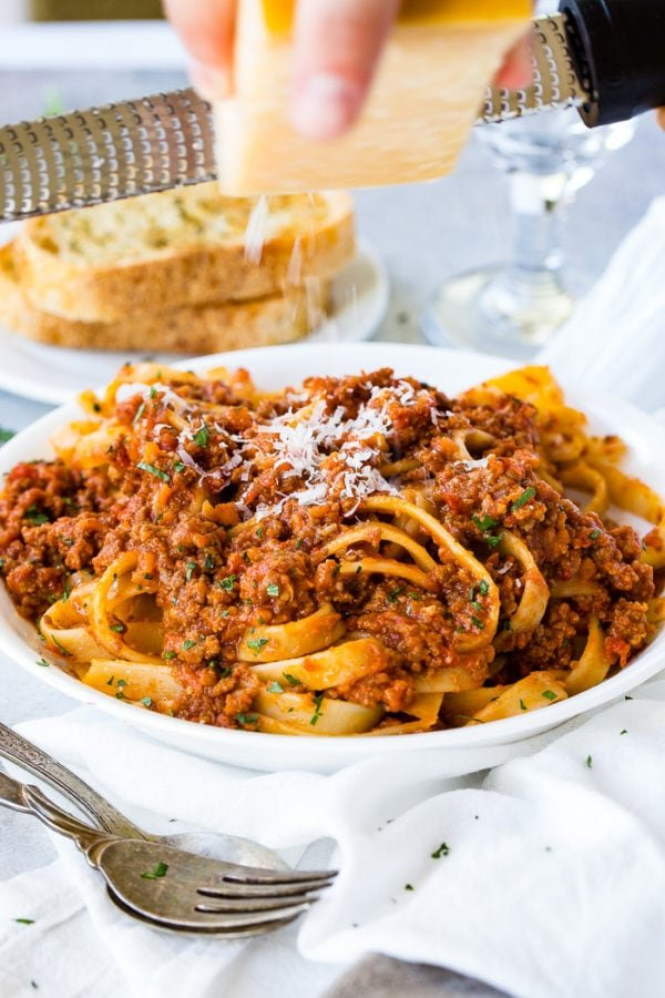 A white pasta dish full of fettuccini loaded with authentic Italian Bolognese sauce and fresh parmesan cheese on top with garlic bread in the background