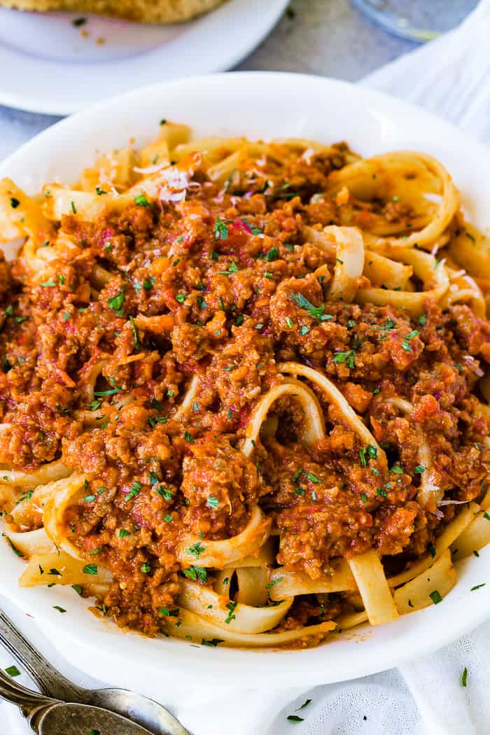 A white pasta dish full of fettuccini loaded with authentic Italian Bolognese sauce