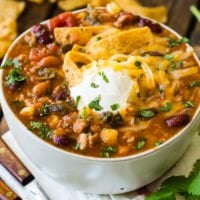 A photo of a bowl of taco chili topped with fritos, sour cream and chopped cilantro.