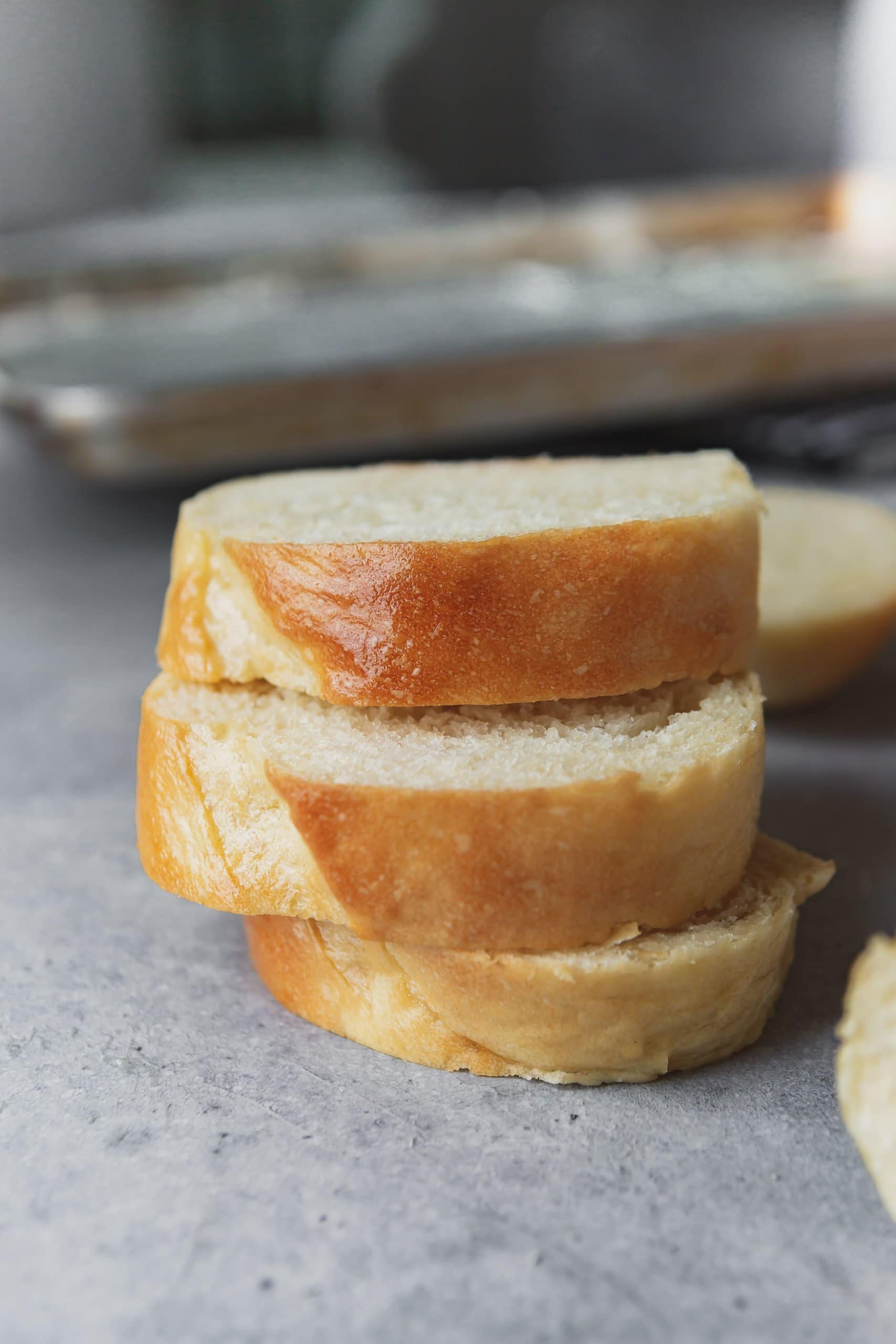 a photo of three slices of french bread stacked on top of each other with the buttery golden top facing the camera..