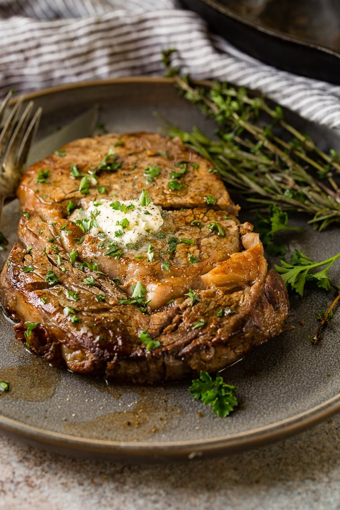 a grey plate with a medium rare ribeye steak being cut into and a fork taking a piece with garlic butter melting on top with parsley