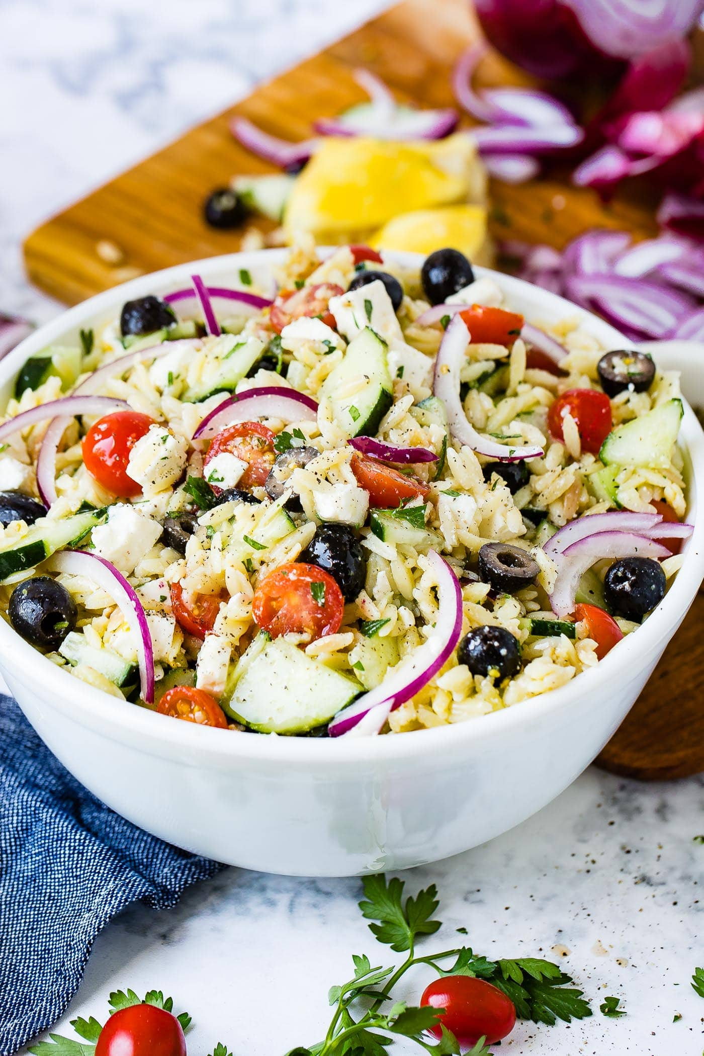 A white bowl full of Greek orzo pasta salad with black olives, cucumbers, cherry tomatoes, slices of red onions and feta cheese.