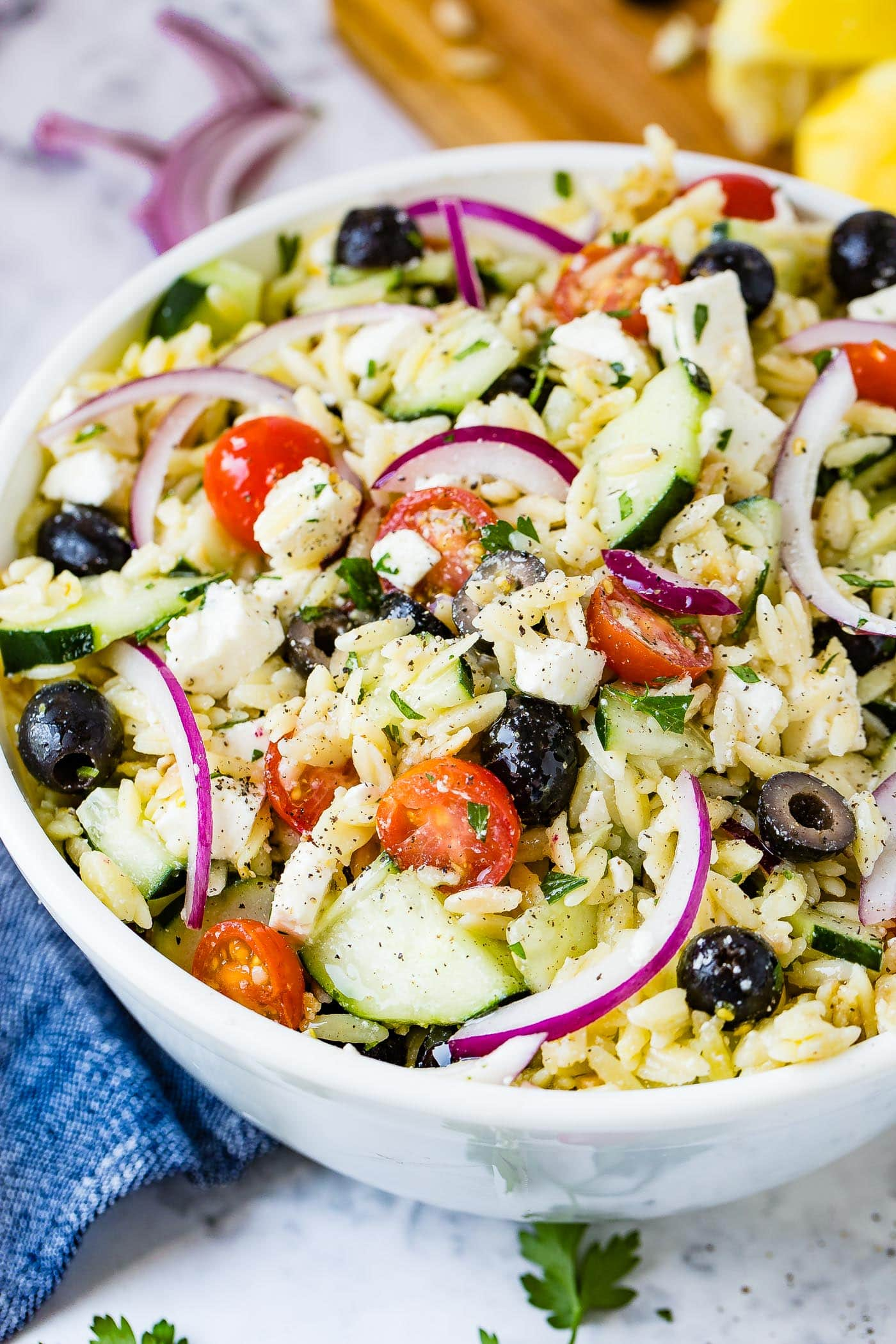 A white bowl of Greek orzo pasta salad with halved cherry tomatoes, slices of red onion, cucumber, black olives and feta cheese.