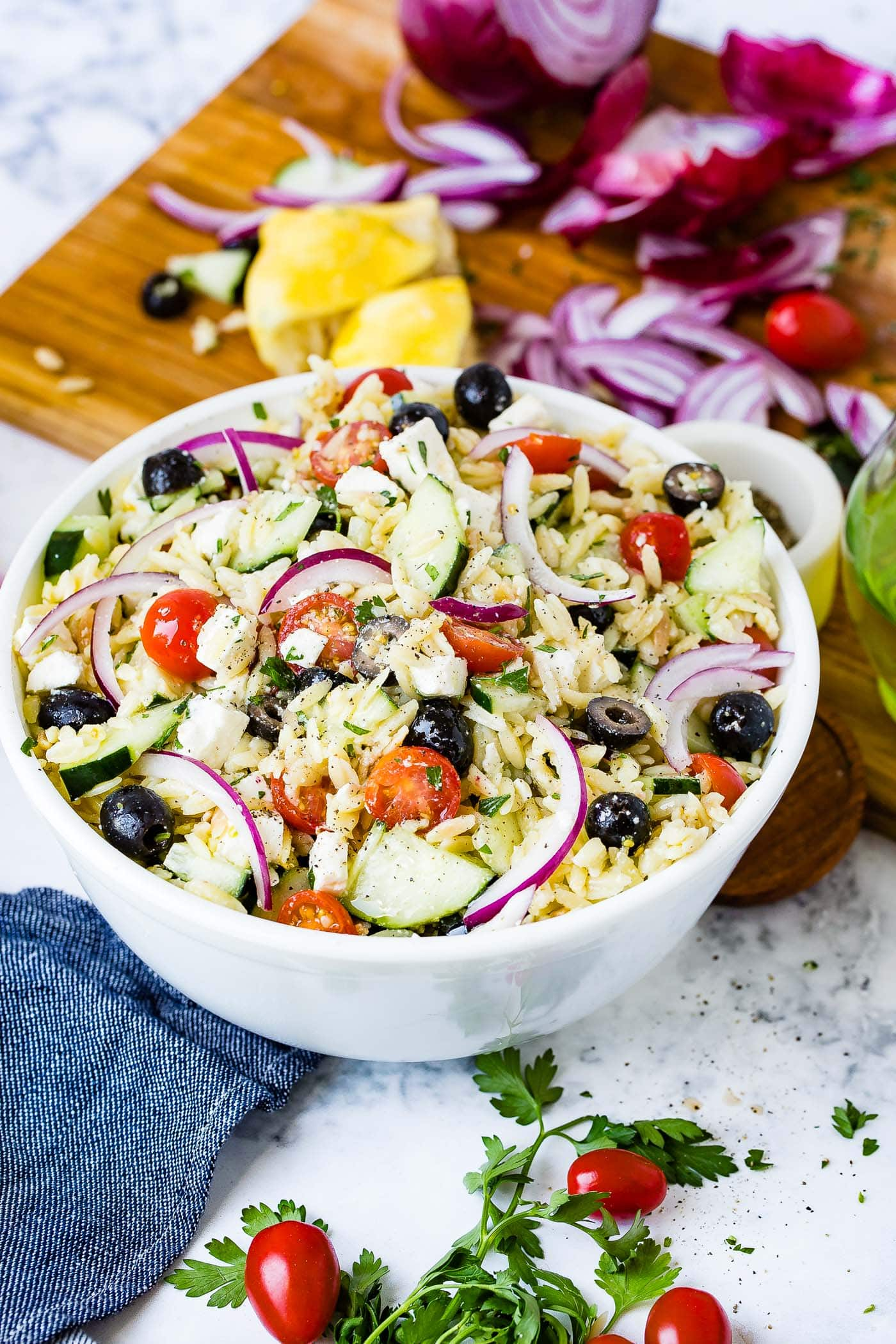 A white bowl of Greek orzo pasta salad with slices of red onion, cherry tomatoes, cucumbers and black olives.