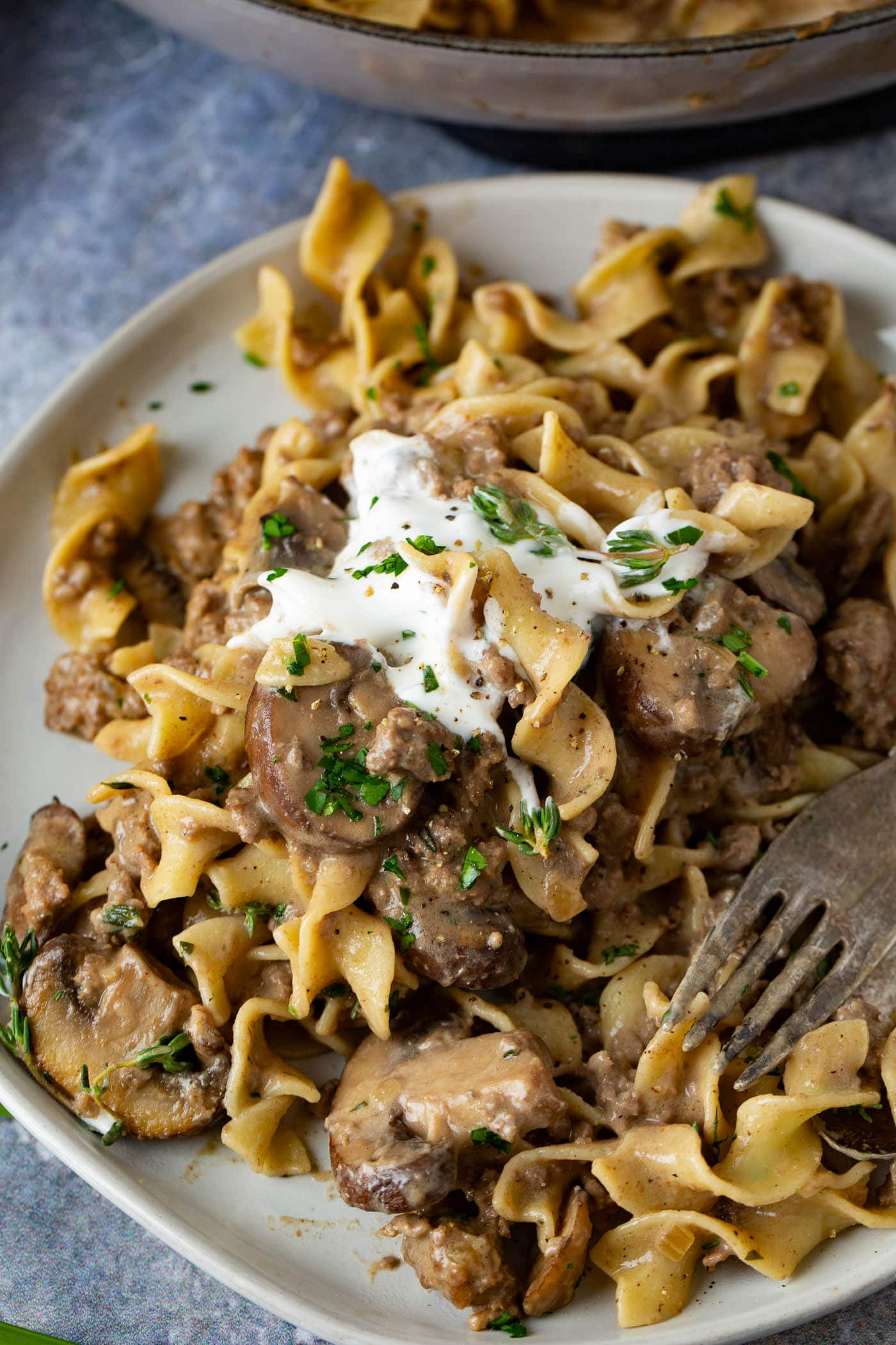 Ground beef stroganoff on a dinner plate. A fork rests on the plate next to the noodles and ground beef stroganoff with a spoonful of sour cream on top.