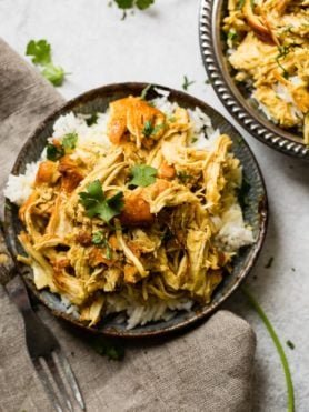 A metal, vintage bowl filled with white long grain rice and shredded chicken with a simple honey curry sauce made in an instant pot with cilantro on top. easy instant pot honey chicken
