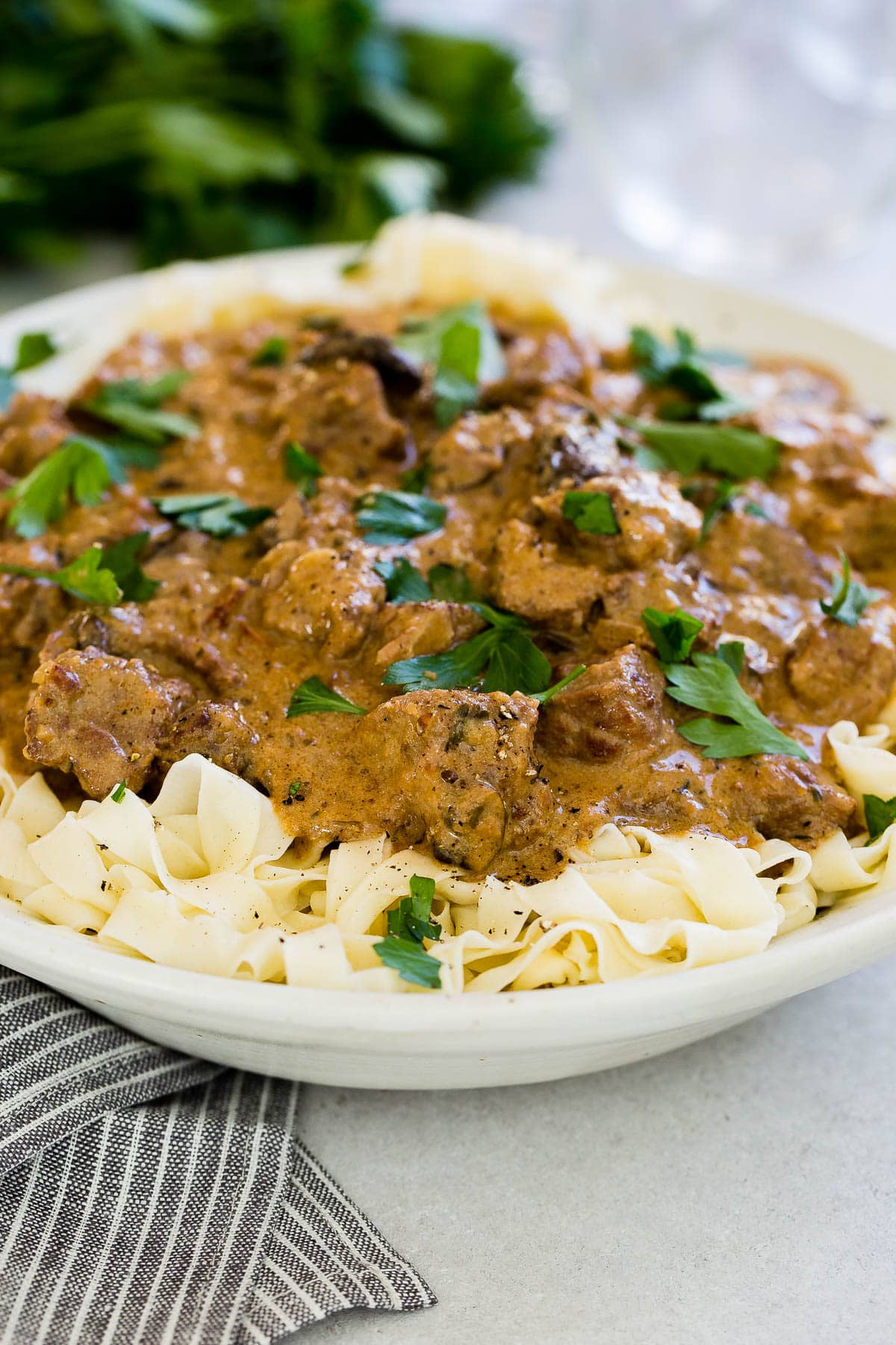 instant pot beef stroganoff atop noodles in white bowl