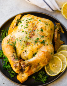 a photo of a roasted whole chicken on a platter adorned with fresh herbs and lemon slices