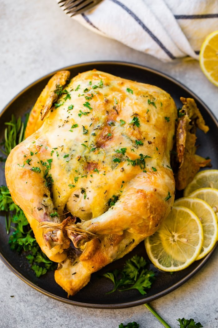 aphoto of a roasted whole chicken on a platter adorned with fresh herbs and lemon slices