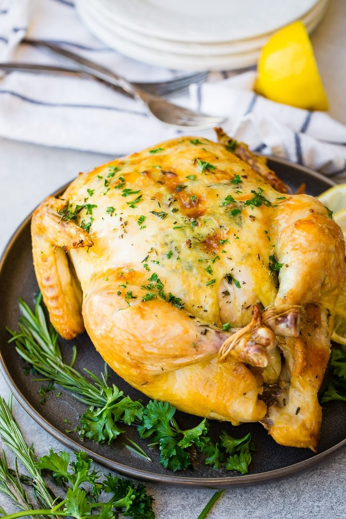 a photo of a roasted whole chicken on a platter adorned with fresh herbs and lemon slices with a half of a lemon and a cloth napkin and fork in the background