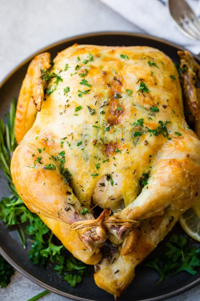 a photo of a golden whole roasted chicken on a serving platter garnished with fresh herbs