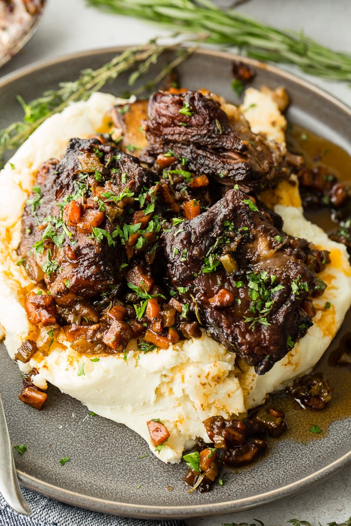 A dark grey plate with a pile of creamy mashed potatoes with fall apart braised beef short ribs and fresh parsley
