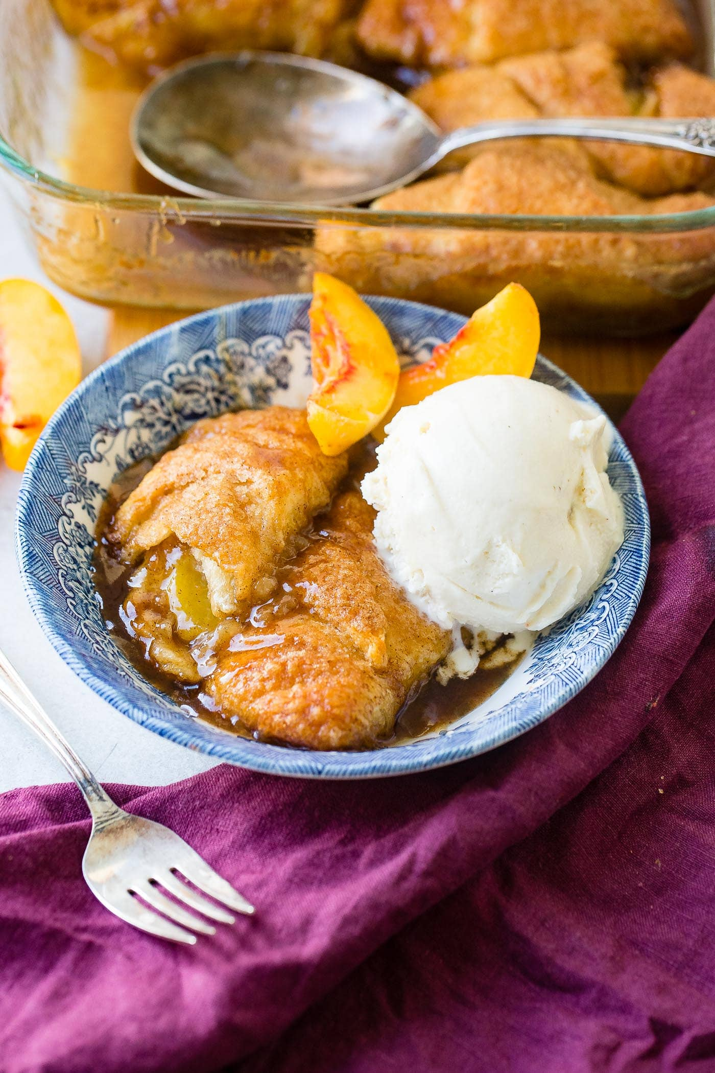 a blue dish on a purple napkin with two peach dumplings and a scoop of creamy vanilla ice cream