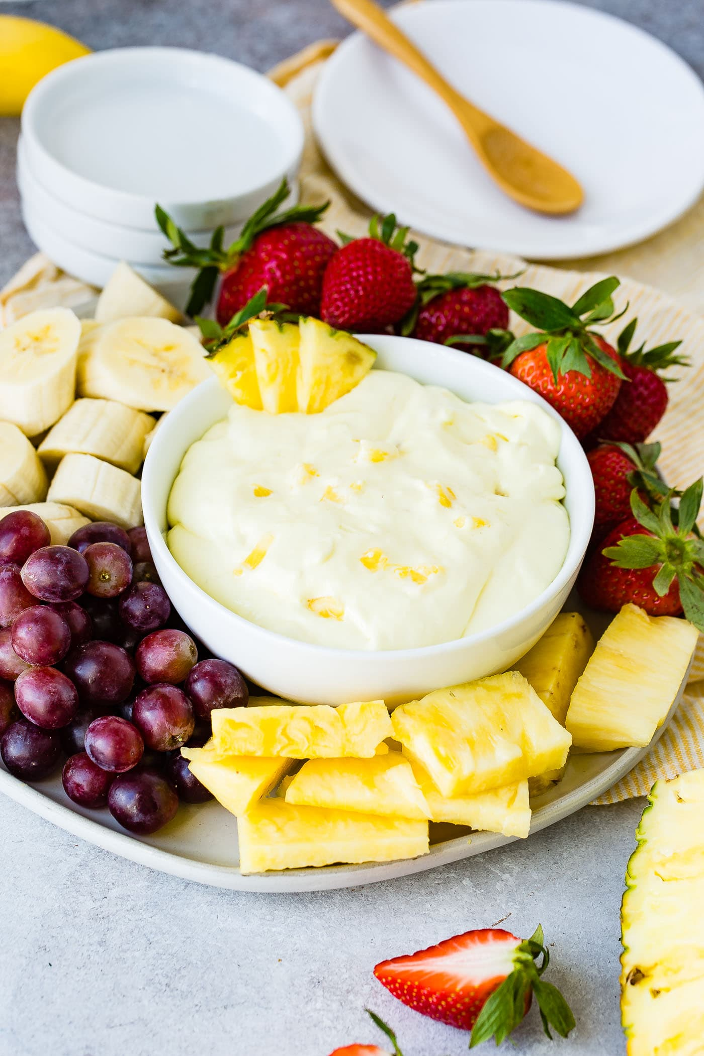 A bowl of pineapple cream cheese fruit dip with three pieces of pineapple on the edge of the bowl. The bowl is sitting on a serving tray with banana slices, red grapes, pineapple chunks, and strawberries surrounding the bowl.