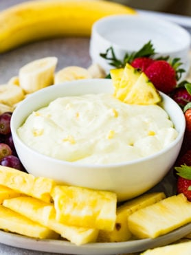 A white bowl containing pineapple fruit dip. There are three chunks of pineapple on the edge of the bowl and tiny pieces of pineapple in the white dip. Sliced bananas, pineapple chunks, and wholes strawberries and red grapes surround the bowl. A banana and a stack of dessert plates are in the background.
