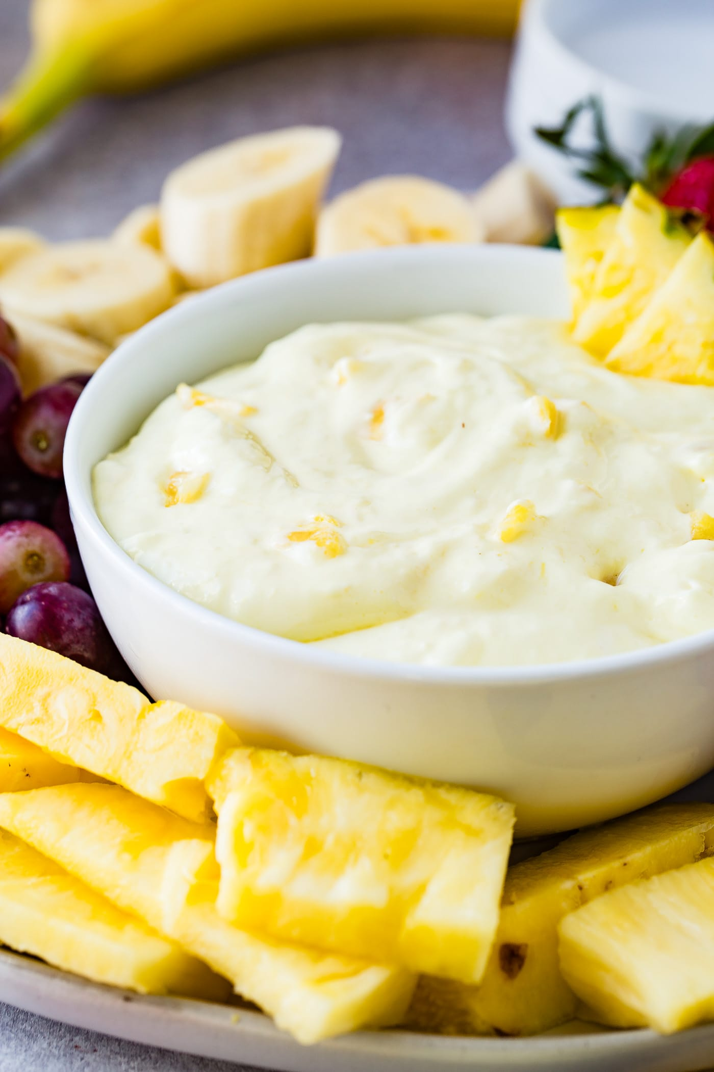 A bowl of pineapple fruit dip with three pineapple chunks on the edge of the bowl and tiny pieces of pineapple in the dip. The bowl is surrounded by sliced bananas, red grapes, pineapple chunks and whole strawberries.