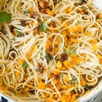 A photo of a large pot full of cooked spaghetti, chopped fresh basil, roasted butternut squash, cheese, and sun dried tomatoes.