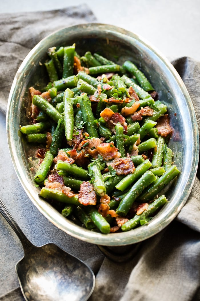 Chopped green beans with crumbled bacon pieces in a silver serving platter next to a grey napkin and vintage silver serving spoon.