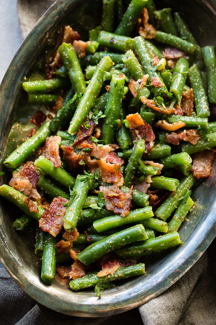 Chopped green beans in a vintage silver serving bowl with crumbled bacon and parsley bits