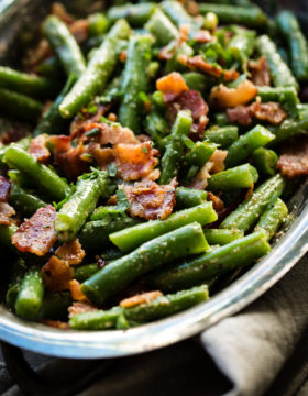 A silver serving dish with bright green beans that have been chopped and served with crumbled bacon ohsweetbasil.com