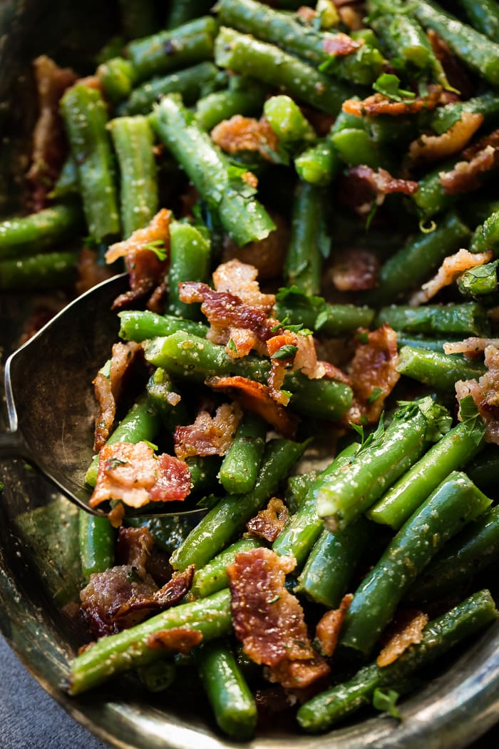 A silver serving platter and silver serving spoon dipping into a bowl of chopped green beans with bacon