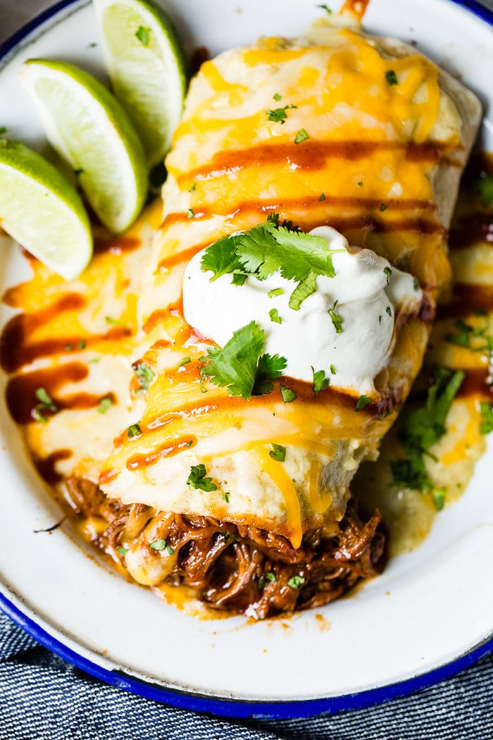 Shredded bbq beef that was made in an instant pot or slow cooker with melted cheese coming out of a burrito topped with sauce, cheese and sour cream and sprinkled with cilantro sitting on a white vintage plate with a blue border