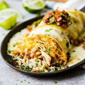 a chicken burrito sitting on a cast iron skillet stuffed with rice, beans and loaded with cheese and salsa on top with a sprinkle of chopped cilantro and limes cut up in the background. smothered honey lime chicken burritos