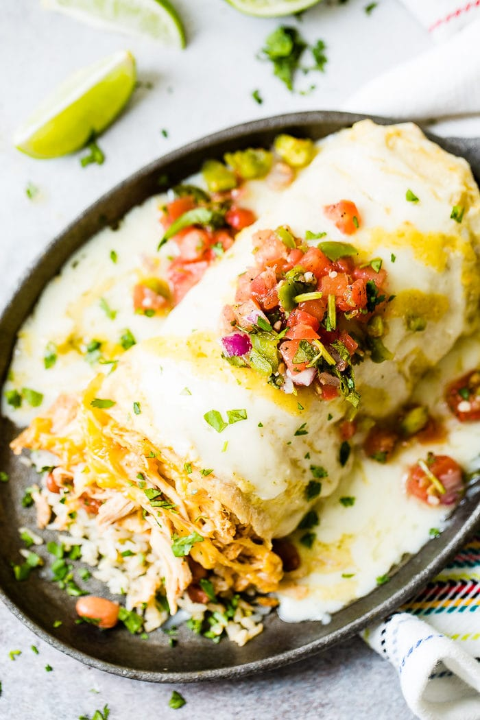 a chicken burrito sitting on a cast iron skillet stuffed with rice, beans and loaded with cheese and salsa on top with a sprinkle of chopped cilantro. smothered honey lime chicken burritos