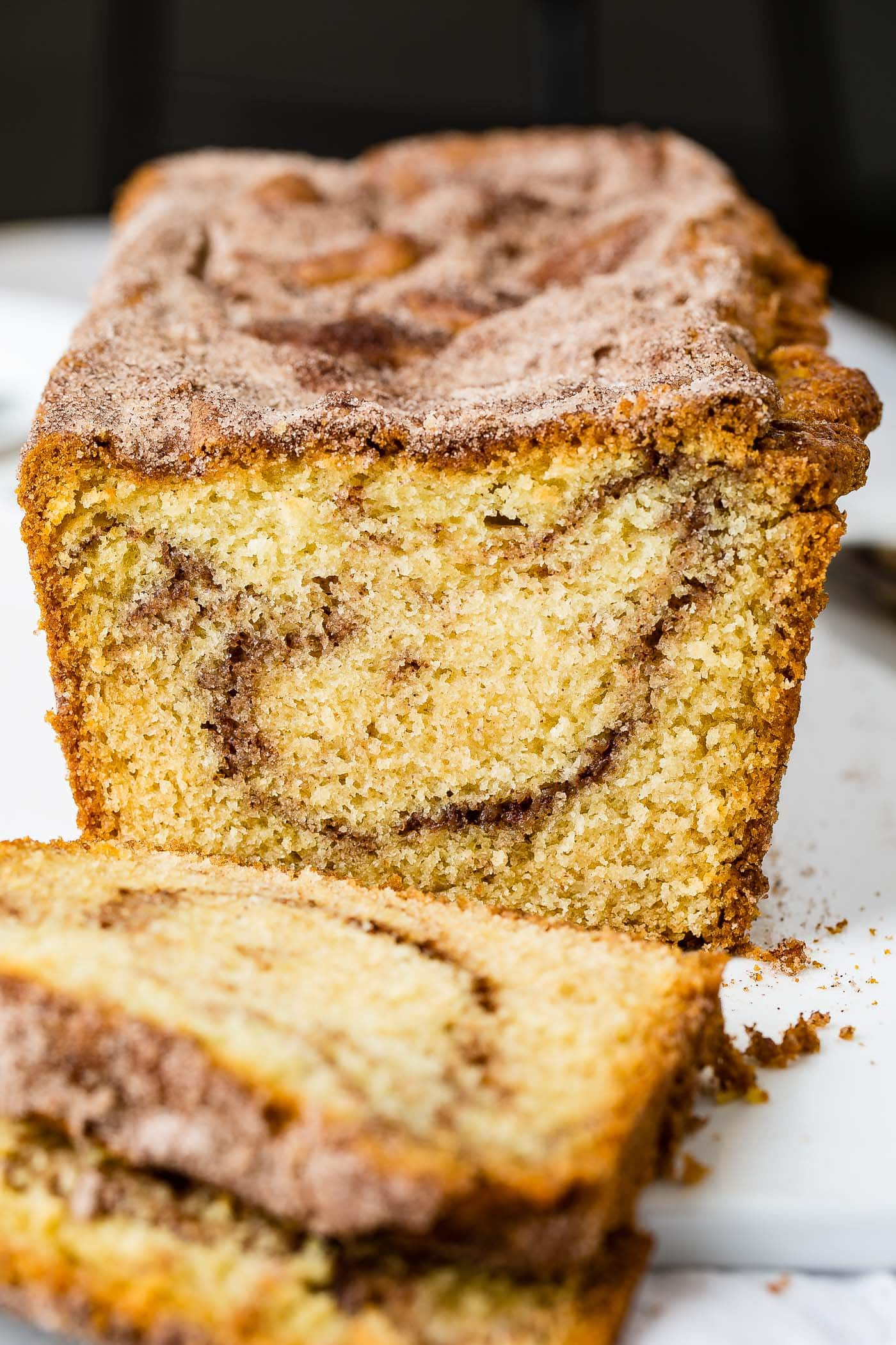 A loaf of snickerdoodle bread that has been partially sliced. There is a swirl of cinnamon sugar in the bread.