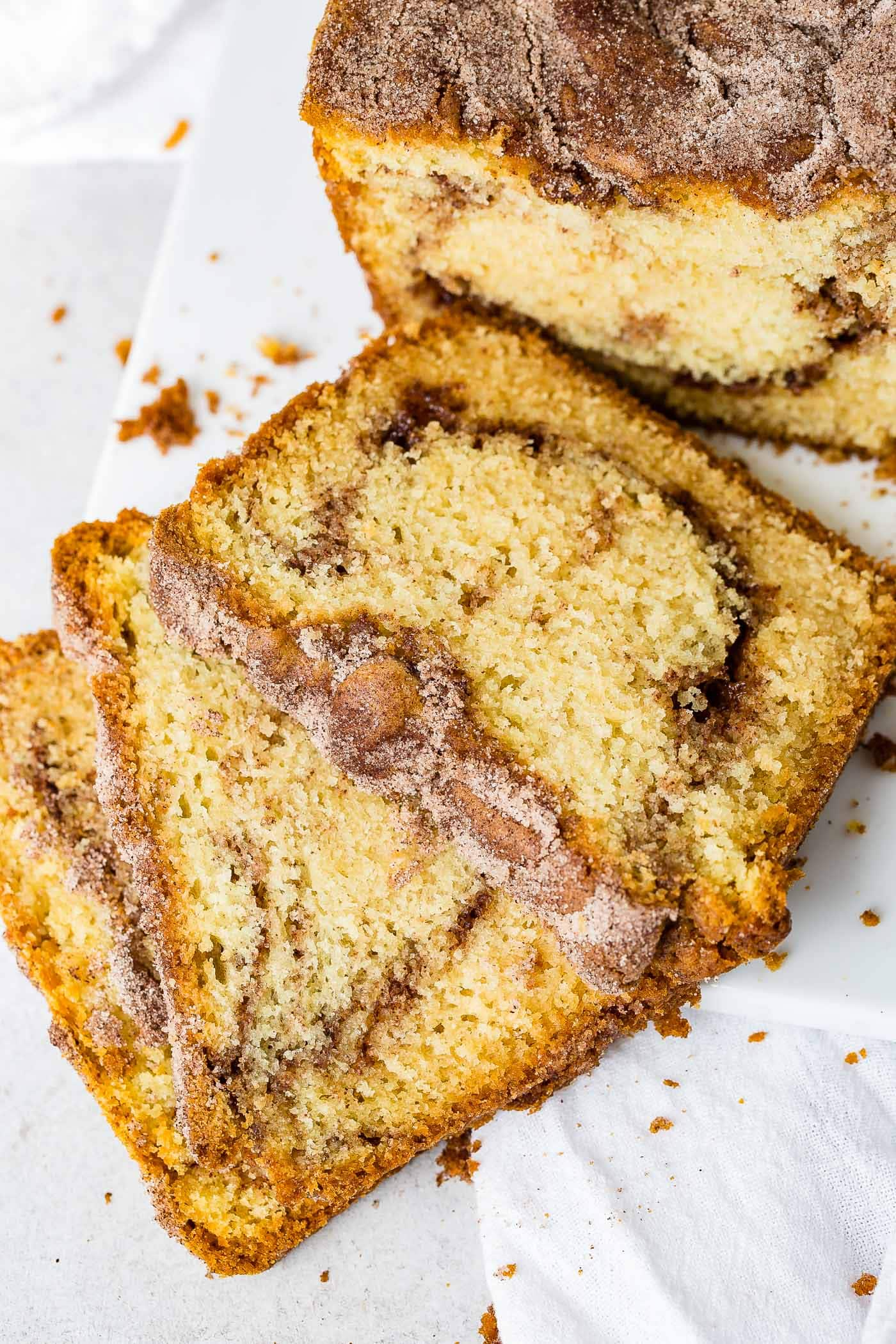 Three slices of snickerdoodle bread laying on a plate with the rest of the loaf of bread in the background.