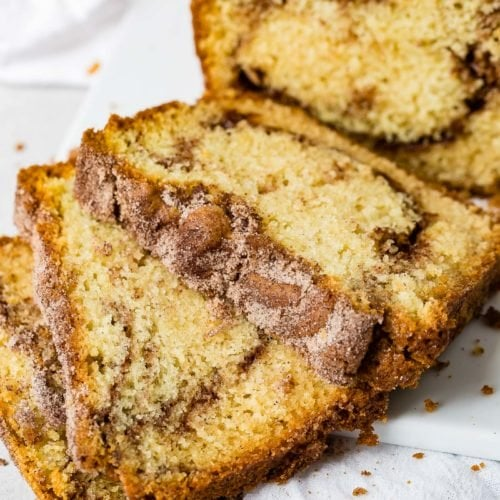Three slices of cinnamon sugar swirled snickerdoodle bread on a plate with the rest of the loaf in the background.