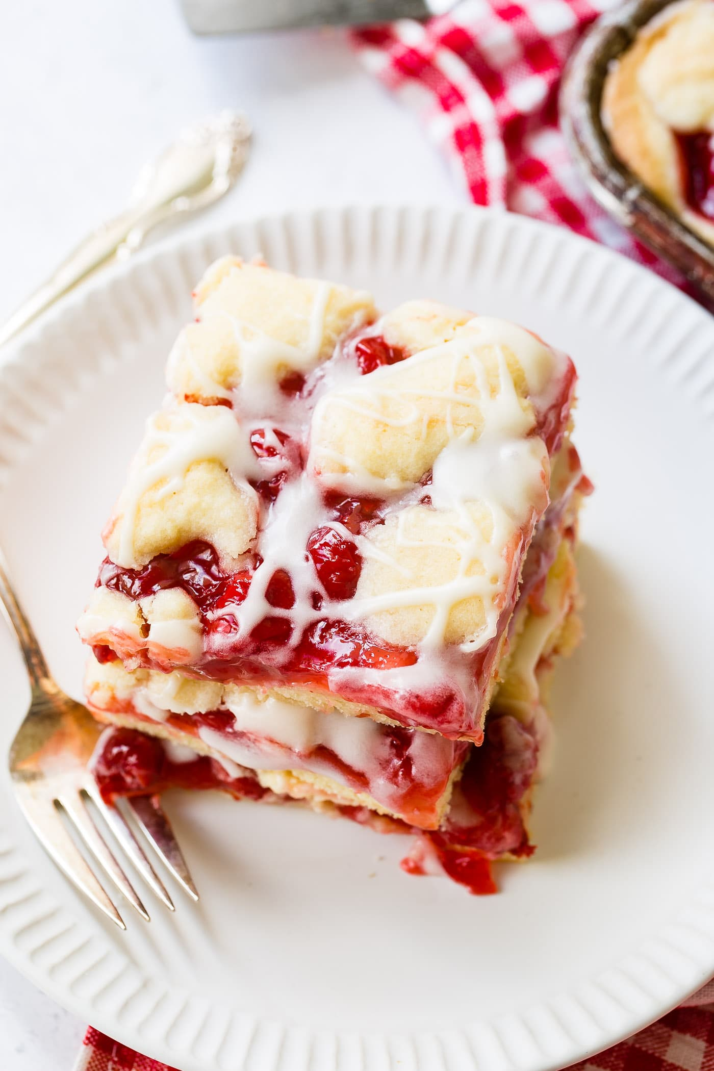 a stack of three cherry pie bars with sweet glaze dripping down.