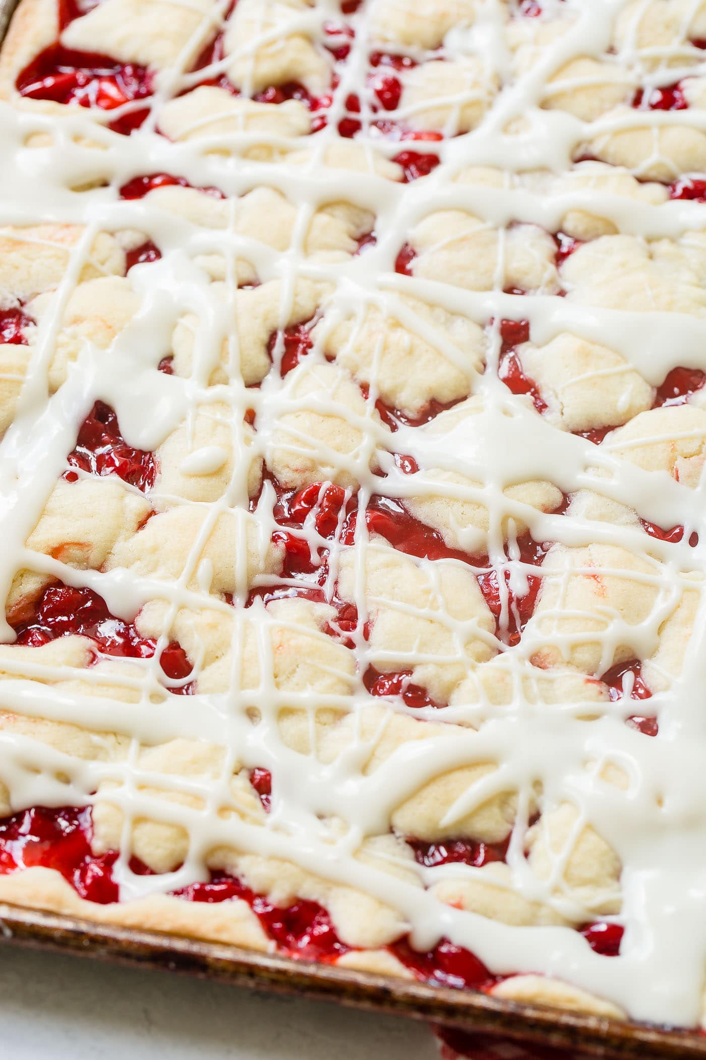 a cookie sheet pan full of cherry pie bars with sweet glaze drizzled over the top