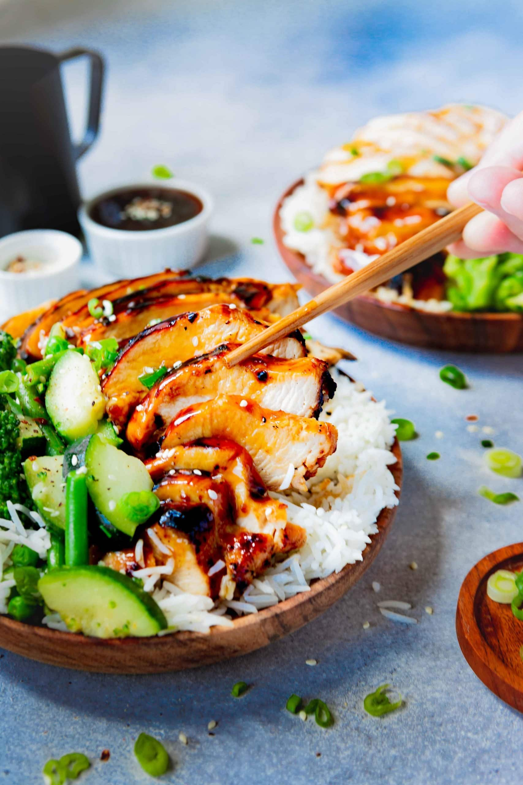 Picture of a plate of white rice topped with delicious teriyaki chicken and steamed green vegetables.  Someone is eating a piece of chicken with wooden chopsticks.
