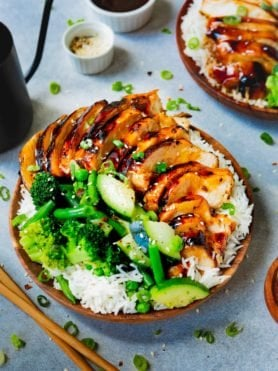 a photo of a plate of rice covered with teriyaki chicken and steamed broccoli and zucchini.
