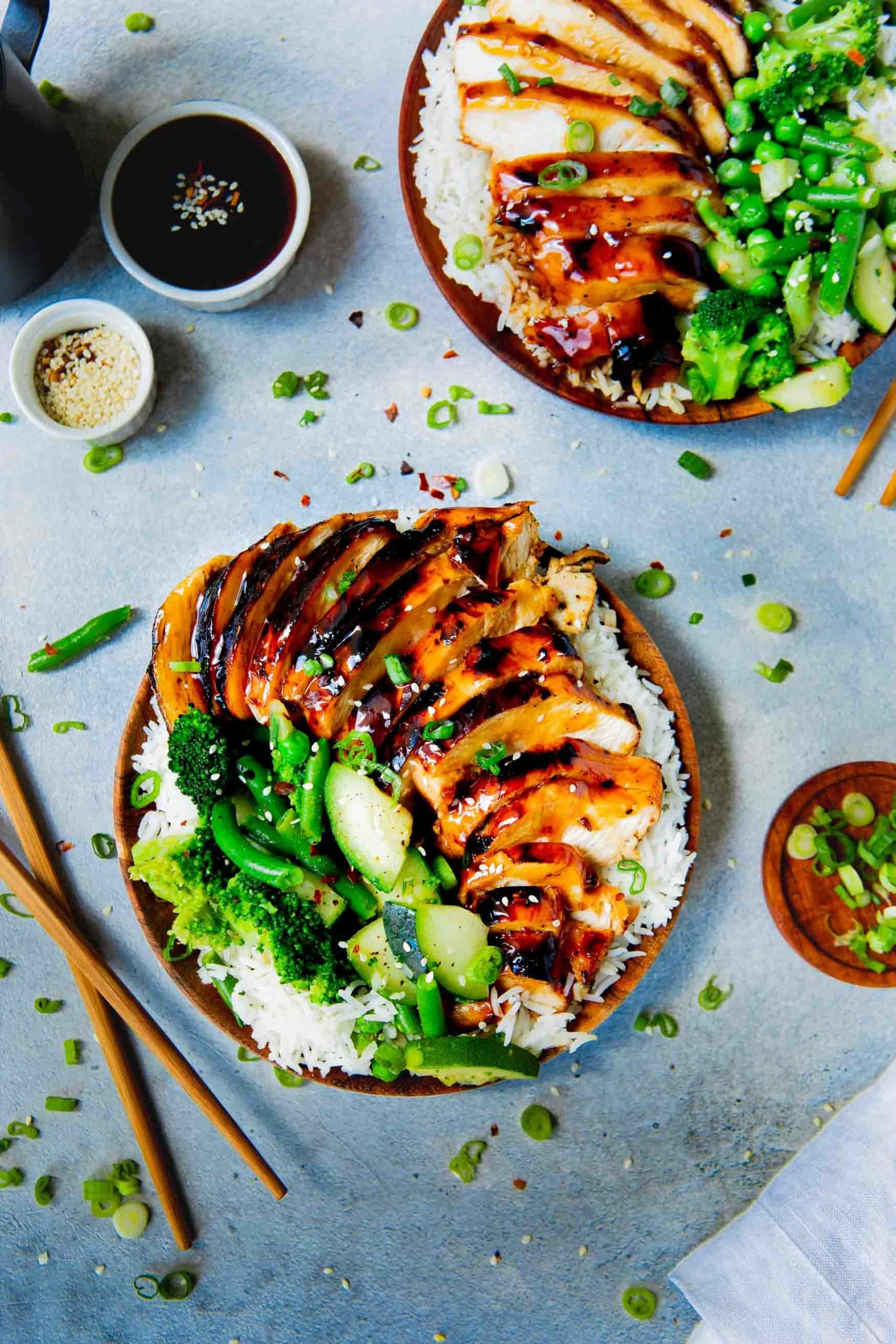 Picture of a plate of white rice topped with tender teriyaki chicken, steamed broccoli, zucchini and green beans with wooden chopsticks next to the plate and another plate of food mostly out of frame
