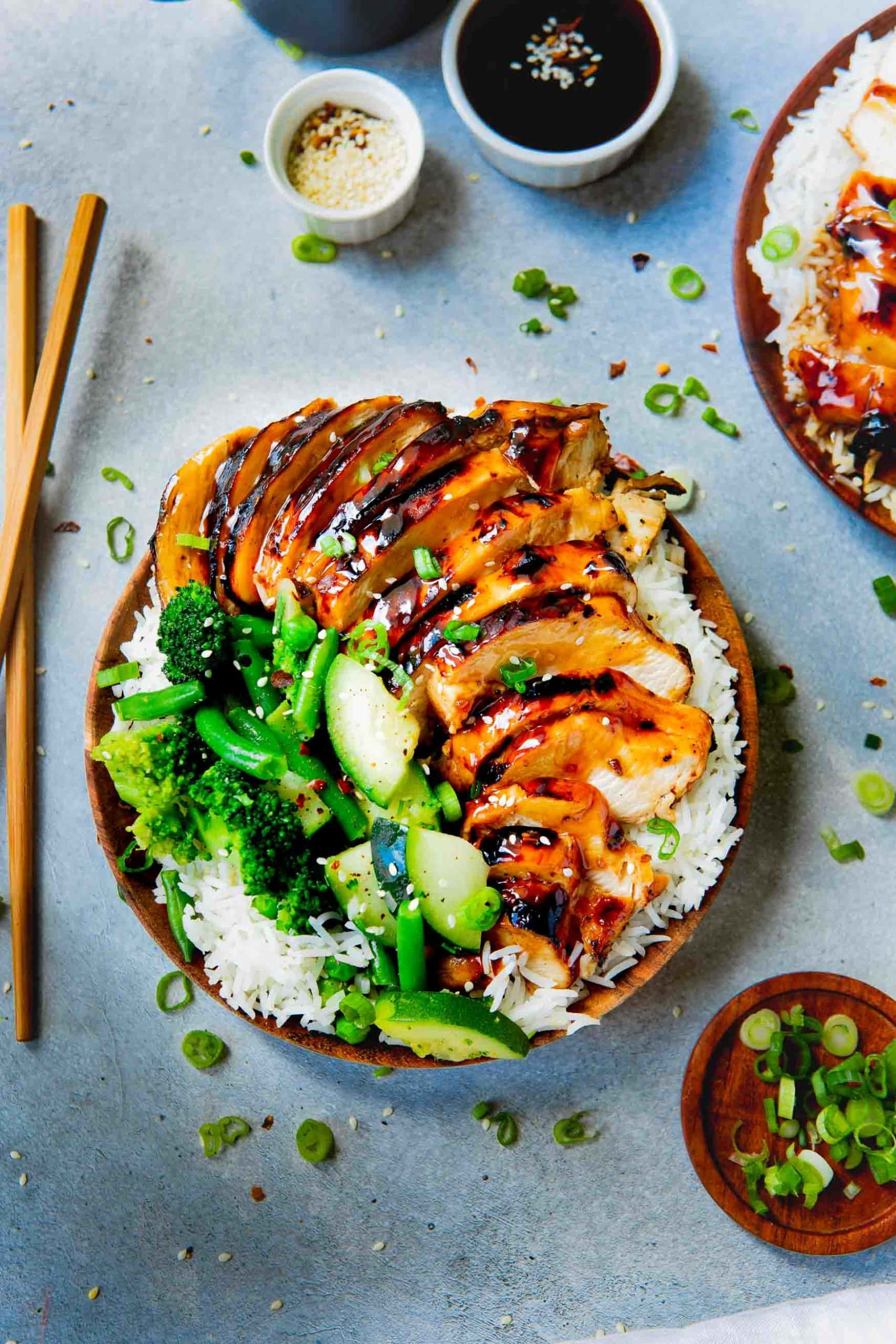 Picture of a rice dish topped with teriyaki chicken with steamed broccoli, zucchini and green beans.